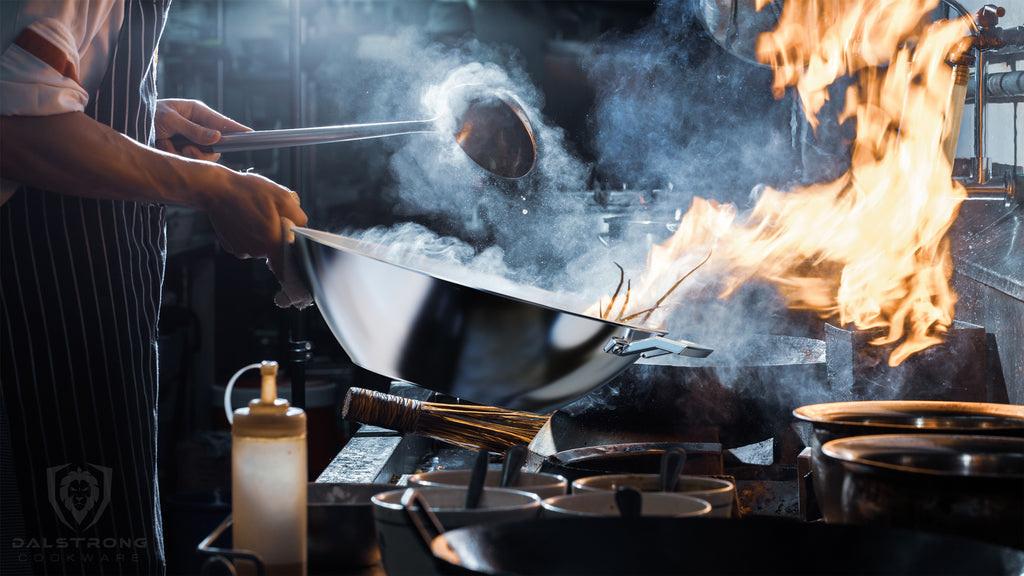 A chef using a smoking wok with flames emerging in a dark kitchen