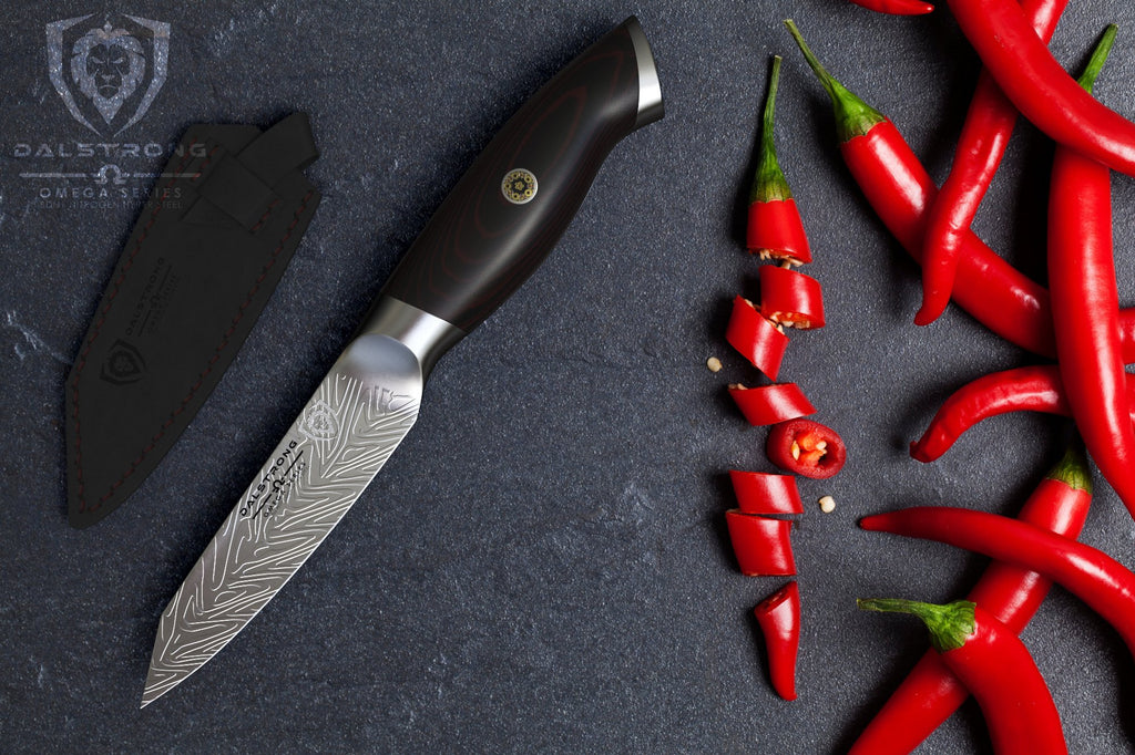 Paring knife on a dark surface next to chopped red chilli pepper