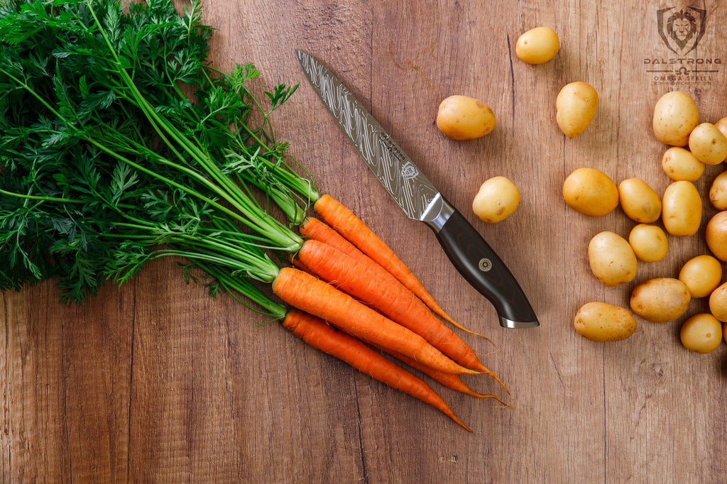Several carrots with green stems next to a sharp utility knife and a pile of small potatoes