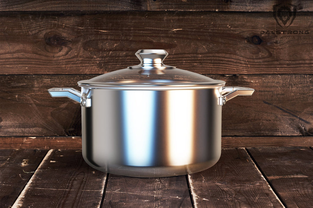 Large shiny silver cooking pot with lid against a dark wood background