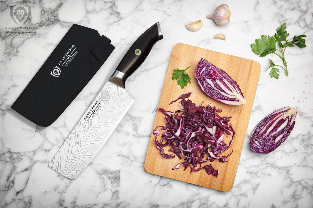 Nakiri knife on marble counter next to a wooden cutting board with diced red onion