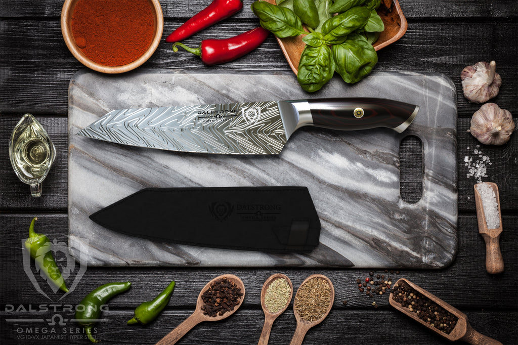 A sharp chef's knife with liquid steel pattern on a stone cutting board surrounded by ingredients
