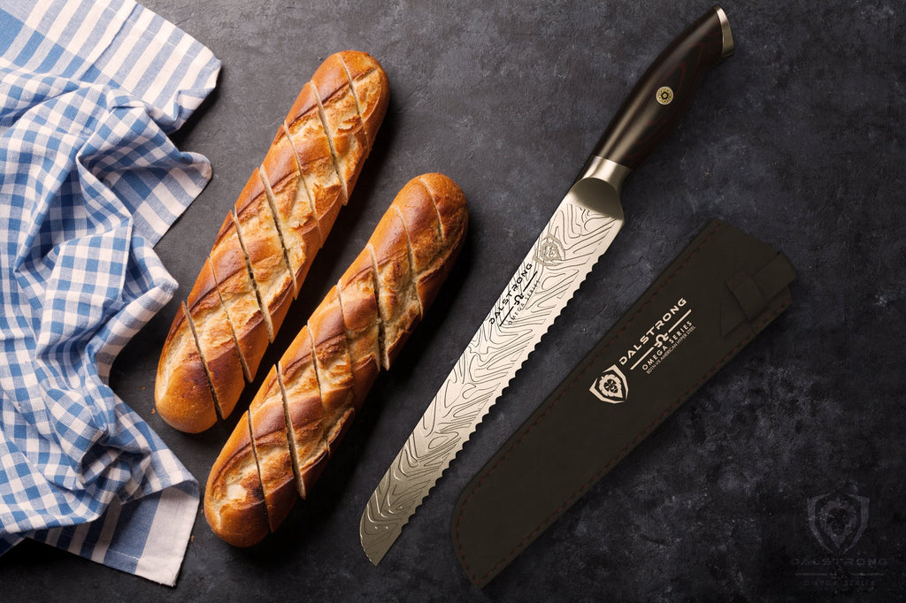 Two bread rolls next to a blue kitchen towel and a stainless steel bread knife on a dark surface