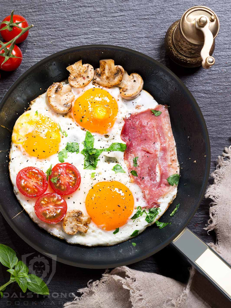 A skillet with fried eggs mixed with bacon tomatoes and mushrooms