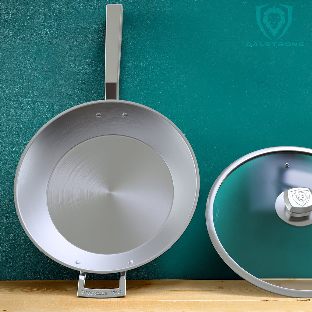 Dalstrong Oberon Series Frying Pan & Skillet Balancing On A Wooden Counter Against A Green Wall