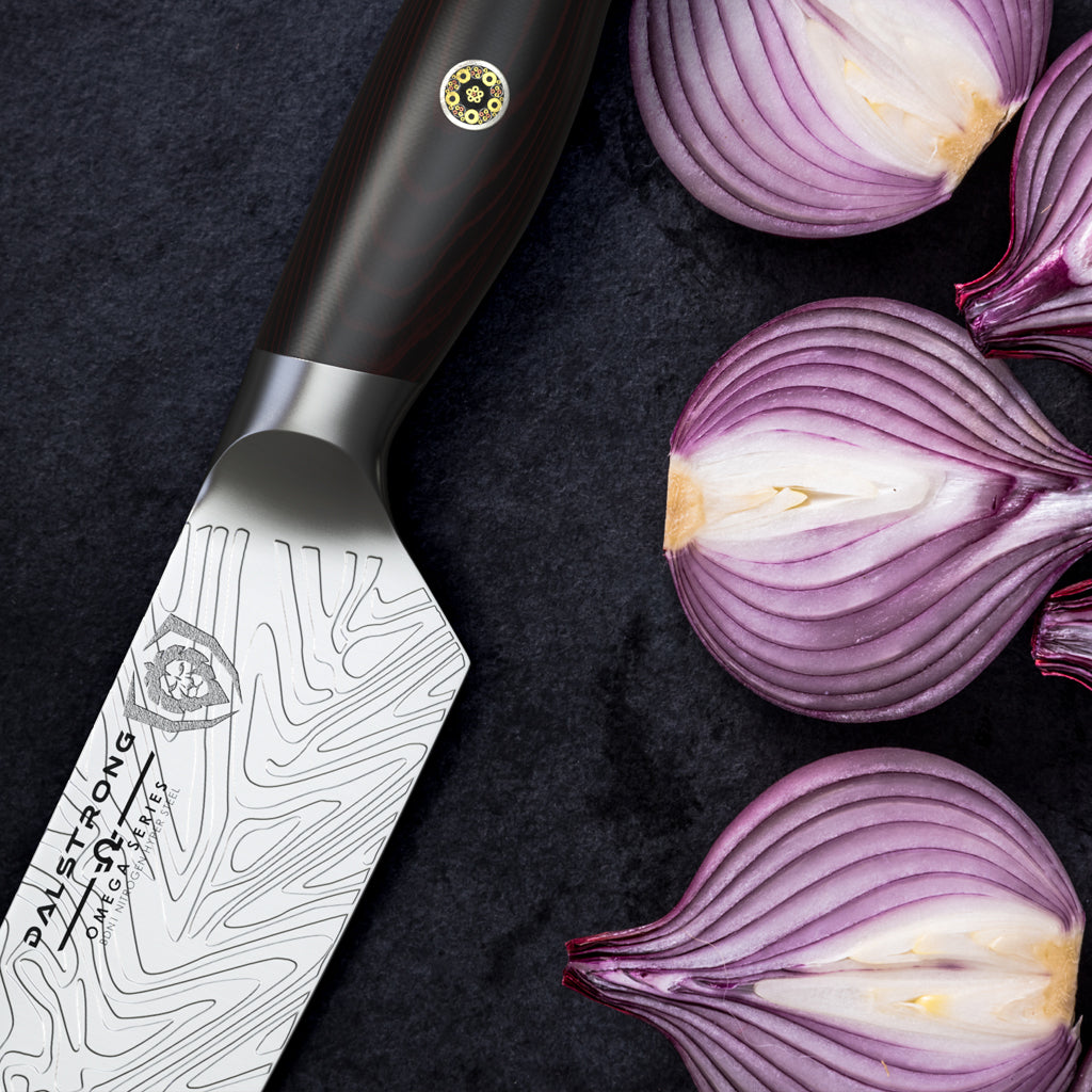 Close up of red onions chopped in half against a black background next to a stylish kitchen knife