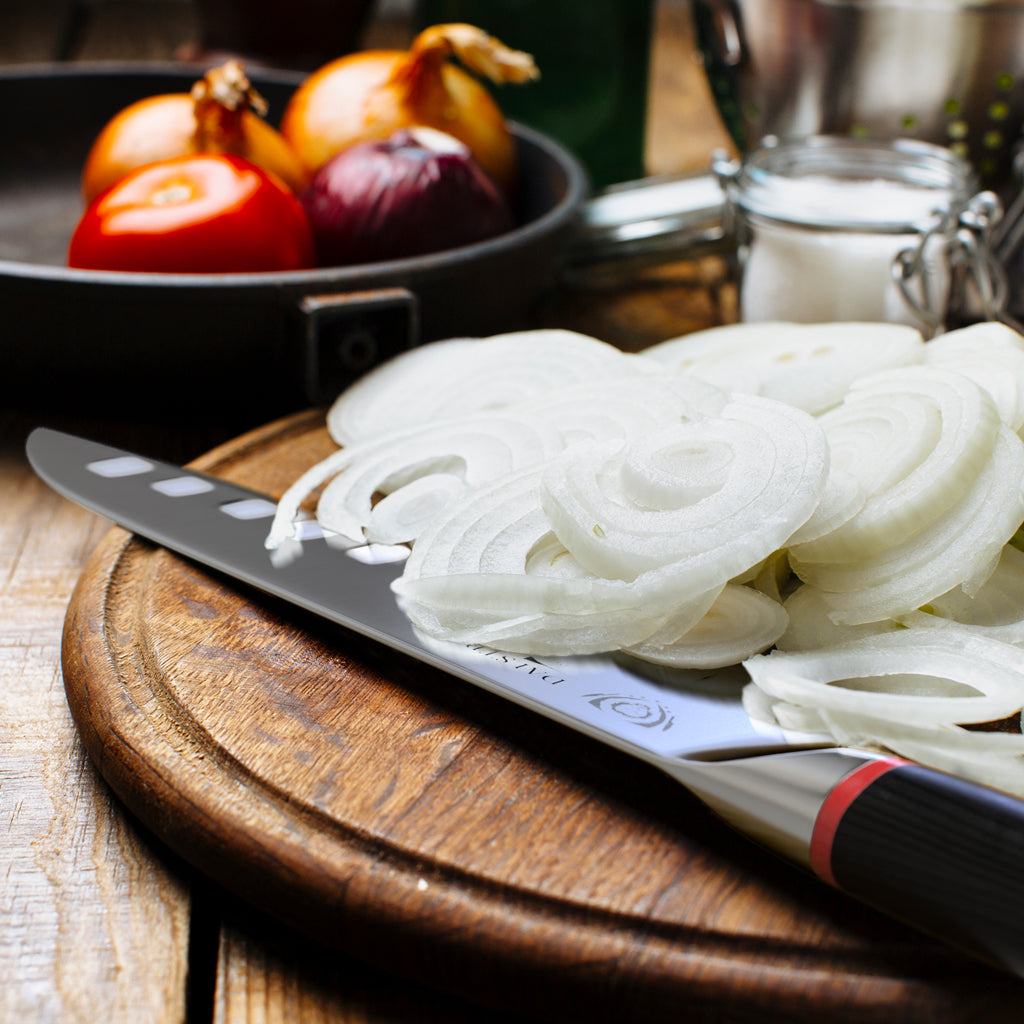 Sliced white onions covering a portion of a Japanese kitchen knife on a wooden cutting board