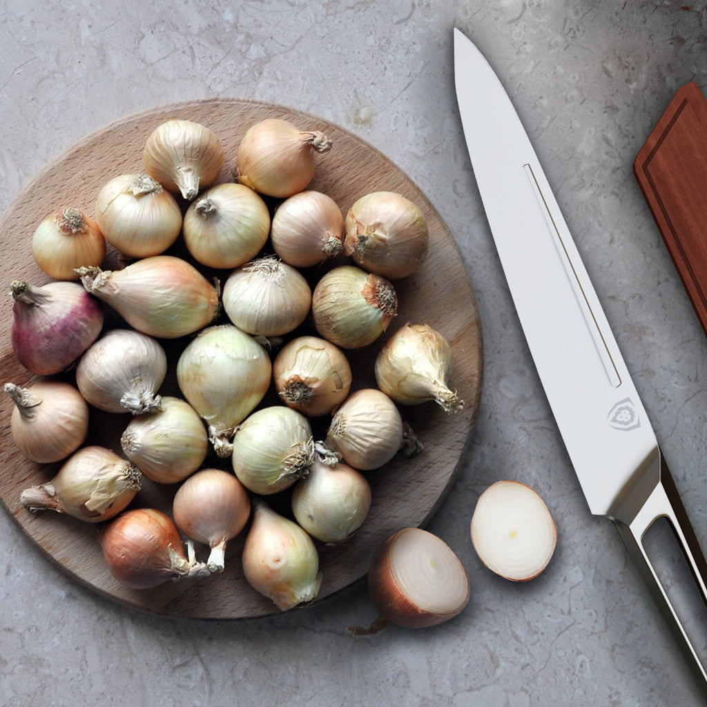 A plate of whole shallot onions next to a stainless steel kitchen knife
