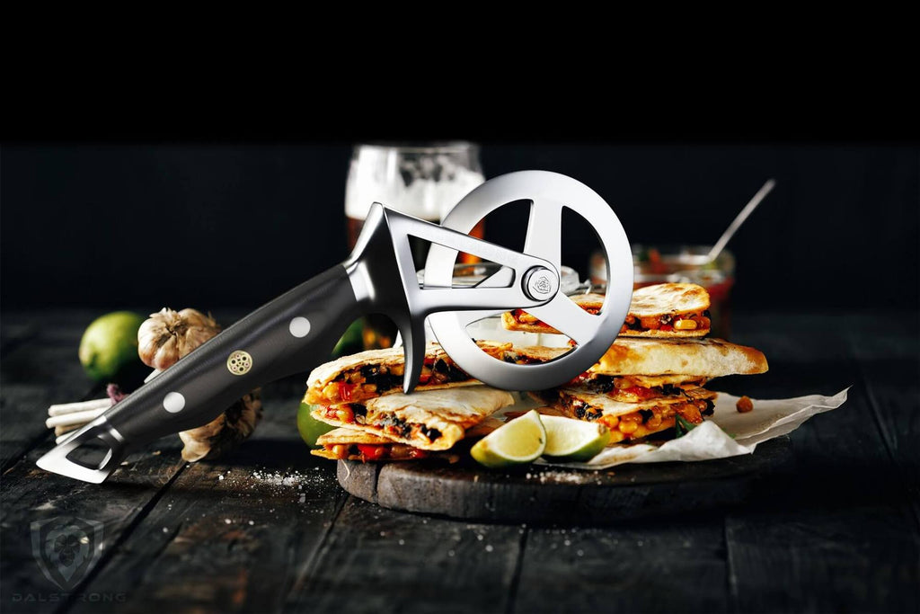 A pizza wheel cutter resting on top of a quesadilla
