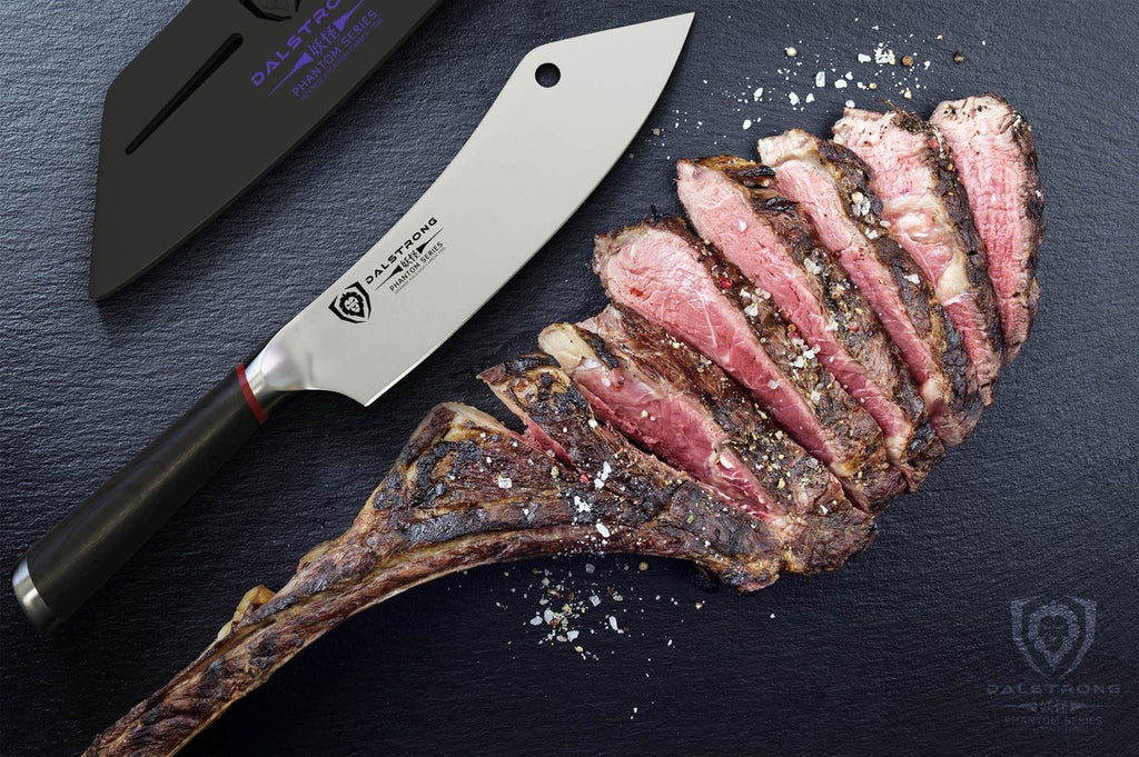 Chinese cleaver next to sliced medium rare meat on a dark surface