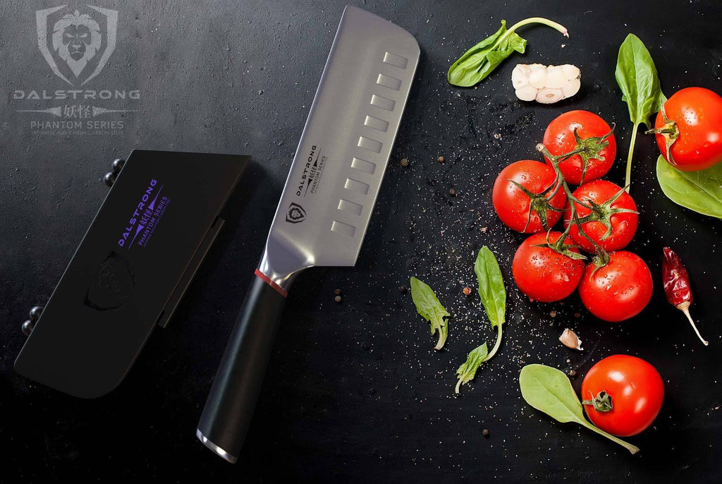 A nakiri knife against a dark grey background next to seven tomatoes on a vine
