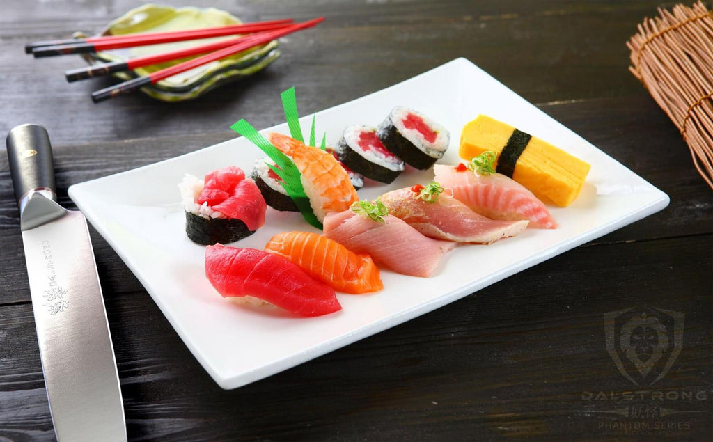An assortment of sushi on a white plate next to a yanagiba knife