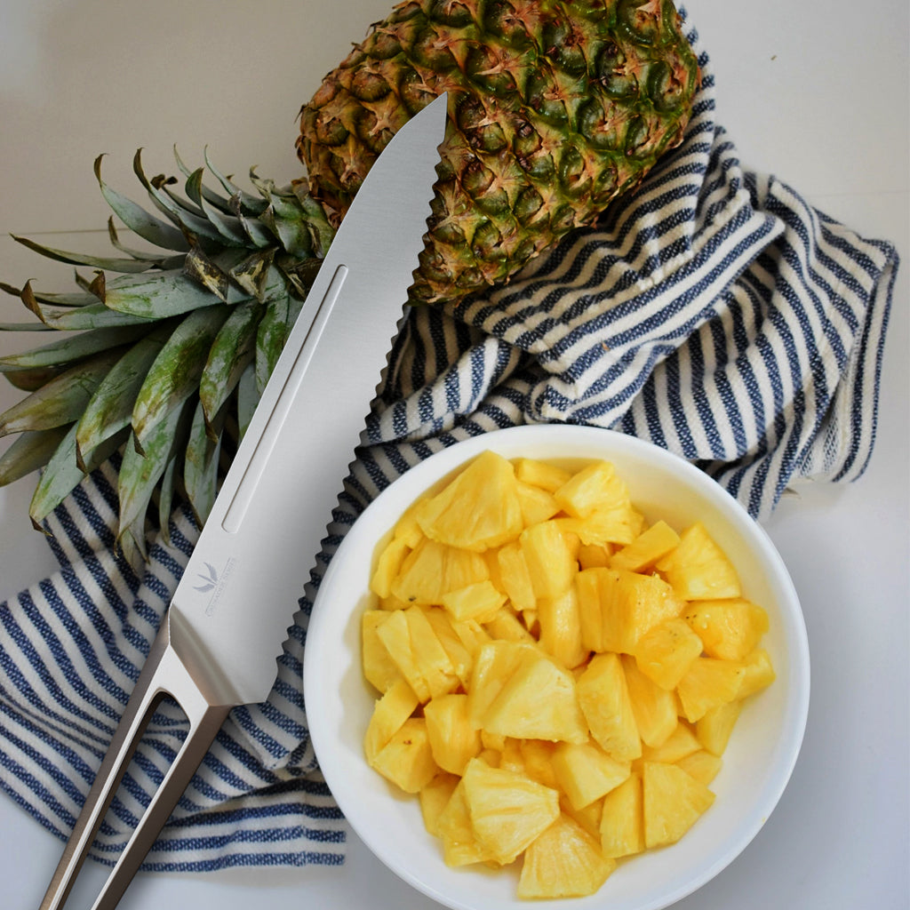 A stainless steel kitchen knife on a back and white kitchen towel next to a small bowl of chopped pineapple cubes