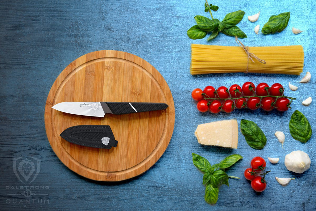 Small paring knife on a circular cutting board next to it's sheath and beside dried pasta and chopped vegetables