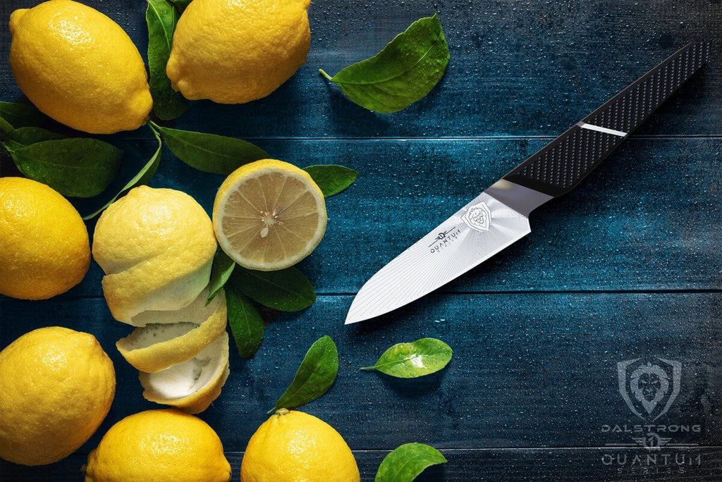 Eight lemons on a blue surface next to a sharp paring knife