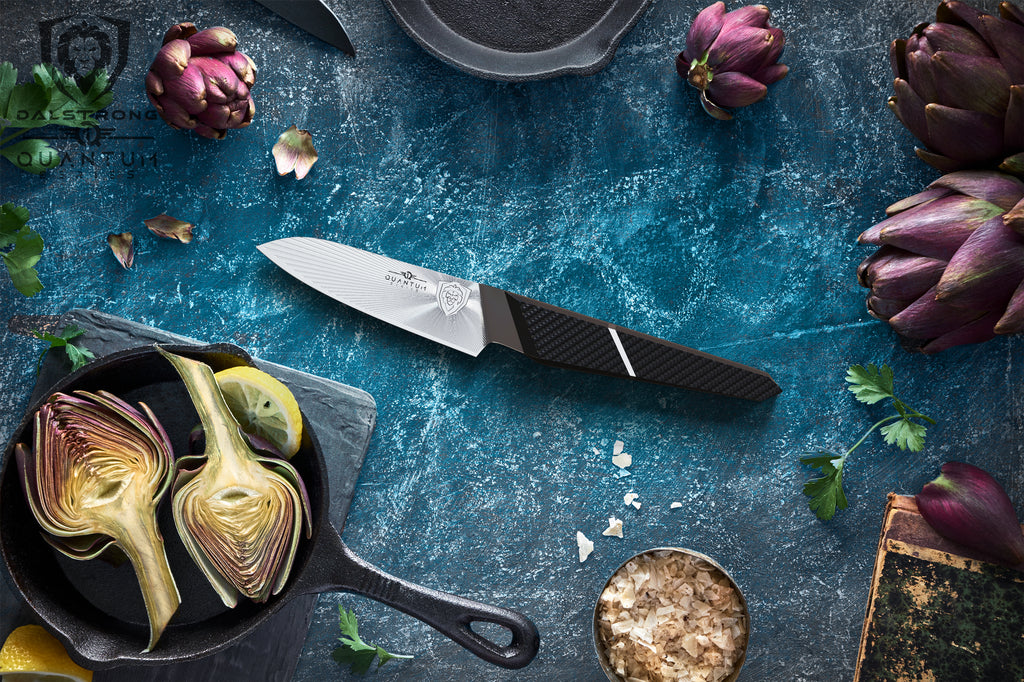 A paring knife against a teal background surrounded by vegetables