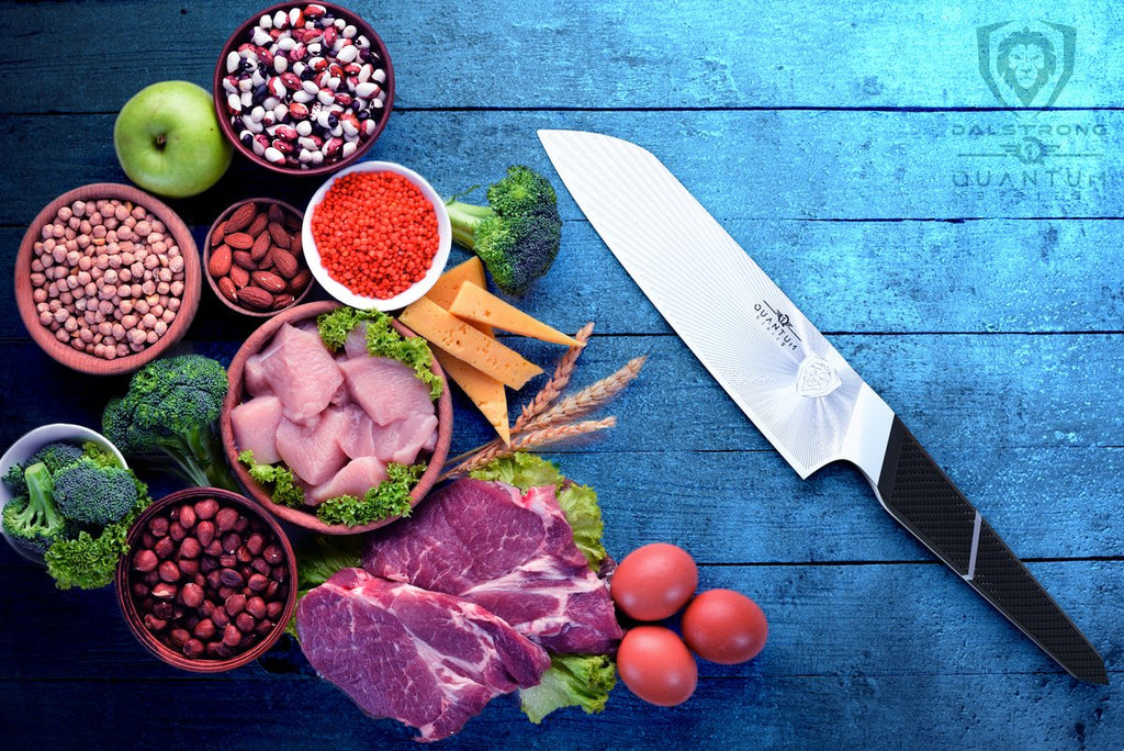 Quantum 1 Series santoku knife on a blue table next to a variety of food including fruit, vegetables and chicken