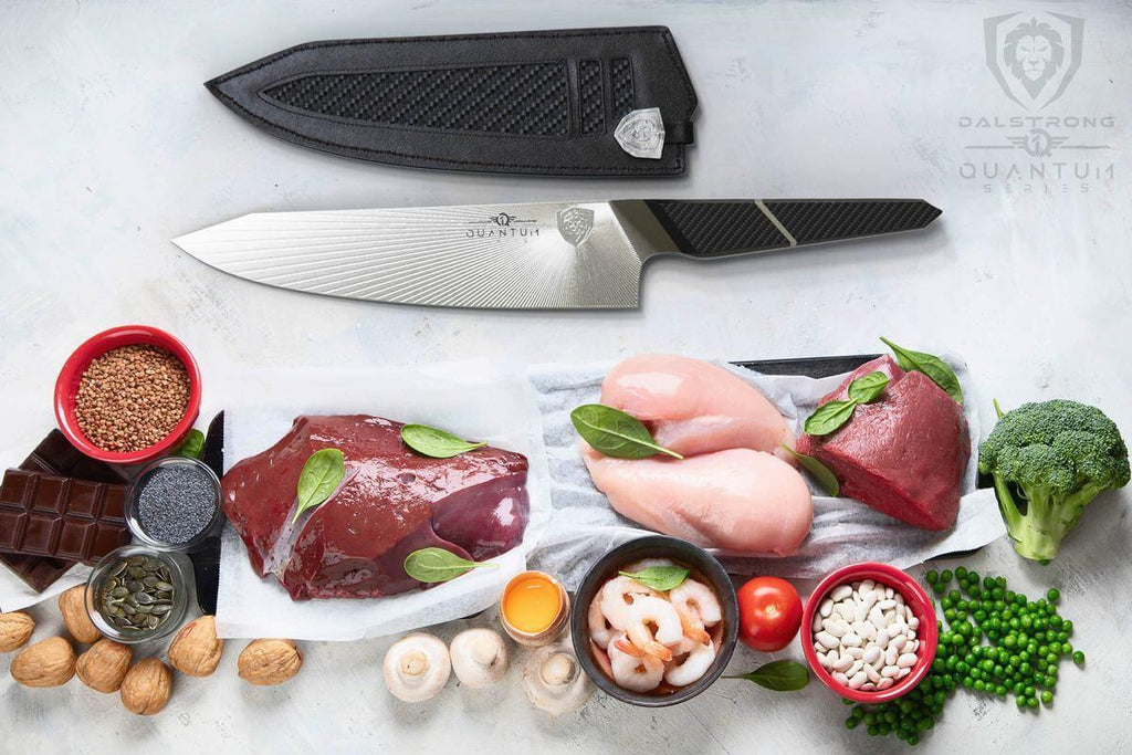 A variety of uncooked vegetables meat and poultry on a white surface next to a kiritsuke knife