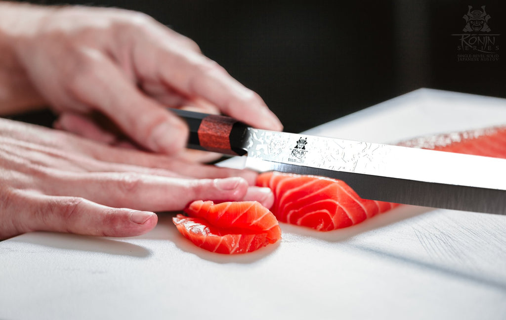 A pair of hands slicing through orange fish with a sushi knife