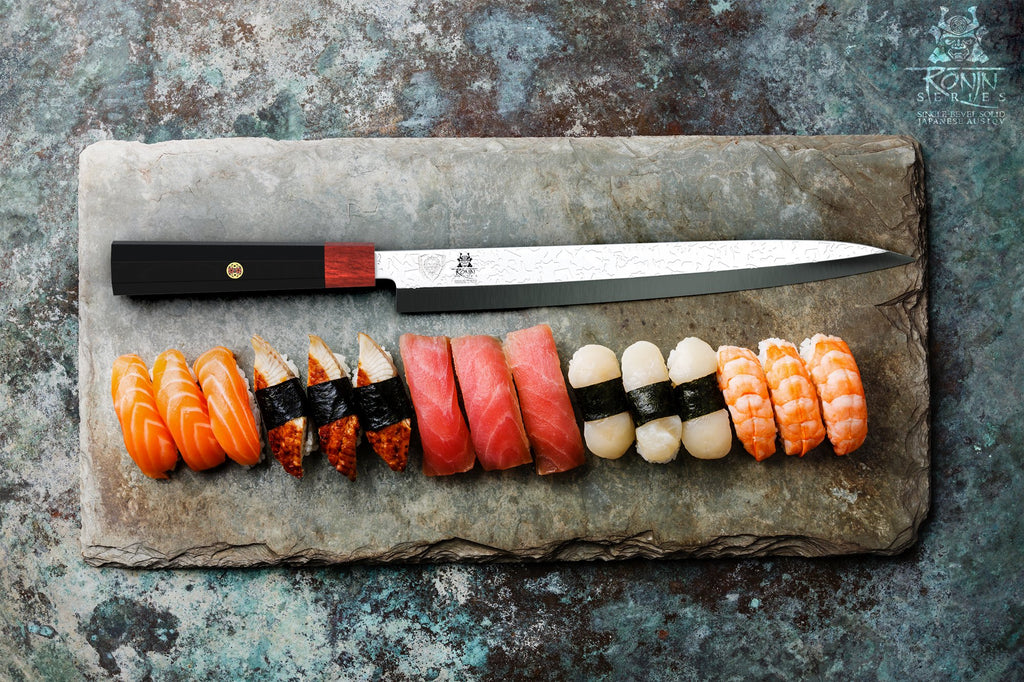 Horizontal yanagiba knife on a marble cutting board in front of several sushi pieces of different colors