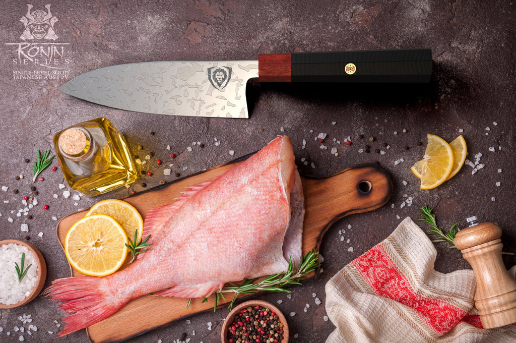 A raw fish on a wooden cutting board next to a sushi knife
