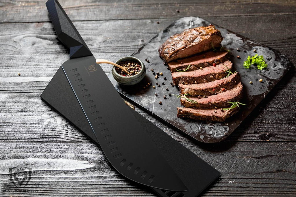 Black bull nose butcher knife next to sliced pieces of cooked meat