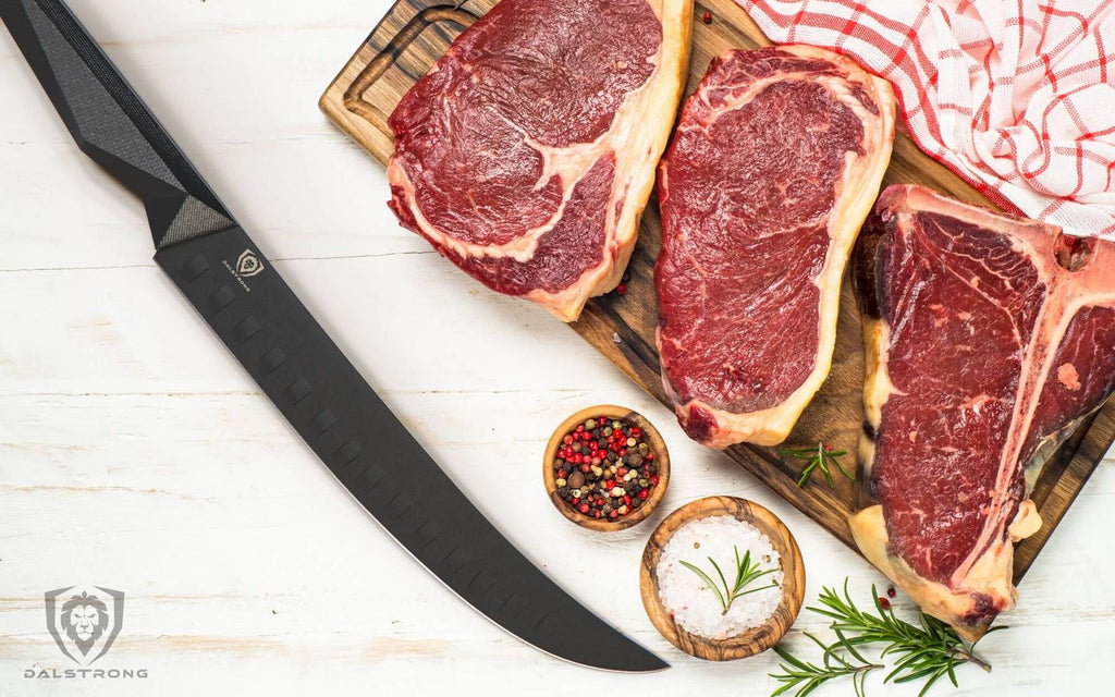 Black butcher knife on white surface next to three large uncooked slabs of beef