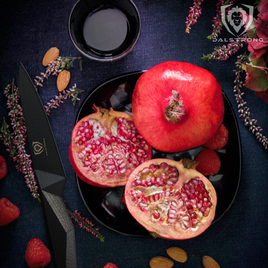 A pomegranate sliced in half next to a small black kitchen knife