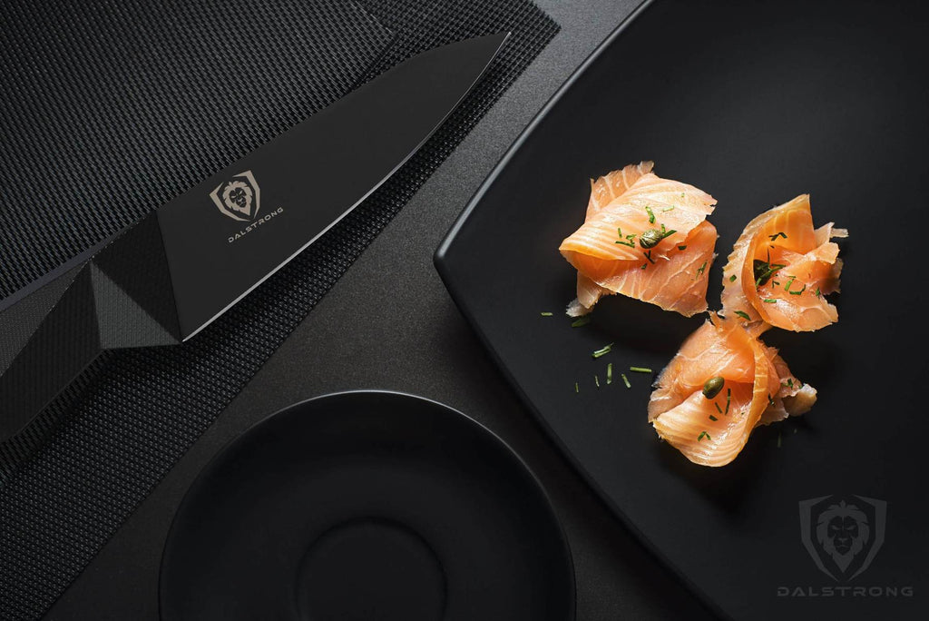 Dark kitchen table with black plate and black paring knife