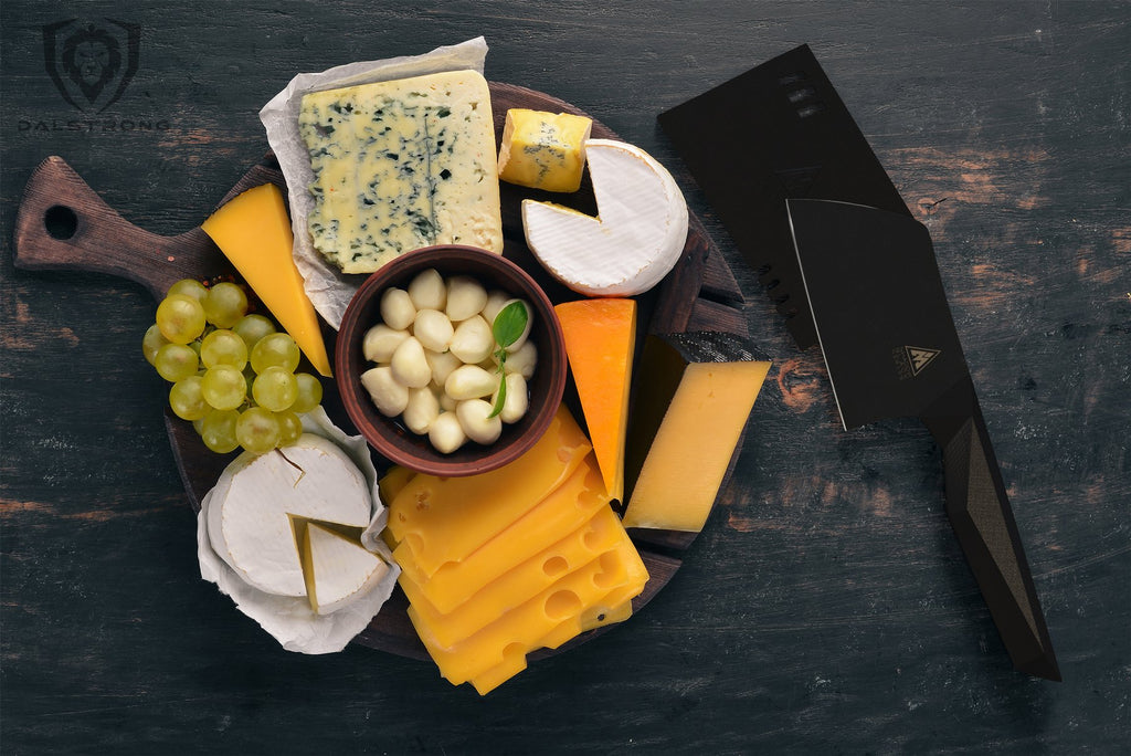 An selection of sliced cheeses garlic and olives on a plate next to a mini black cleaver