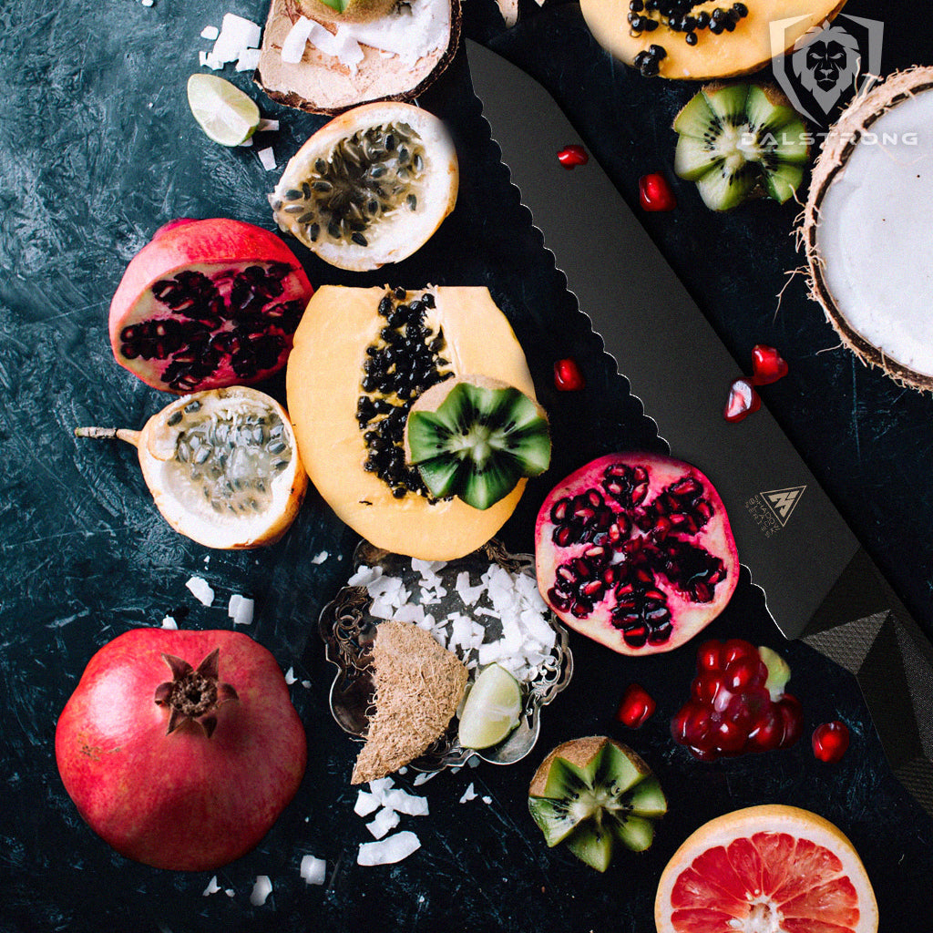A selection of fruits including pomegranate next to a serrated black kitchen knife
