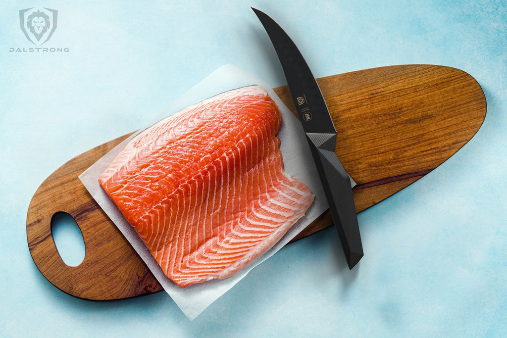 Uncooked fish on a wooden cutting board beside a black fillet knife with a light blue surface