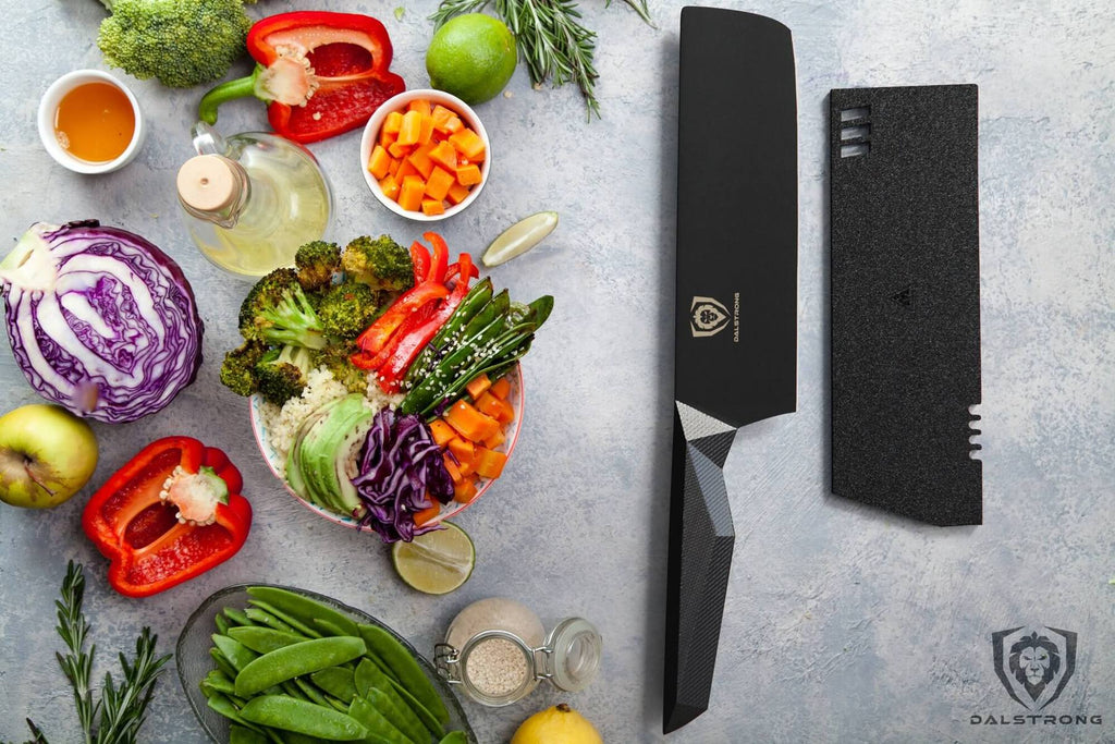 A wide variety of chopped vegetables on a grey surface next to a black nakiri knife