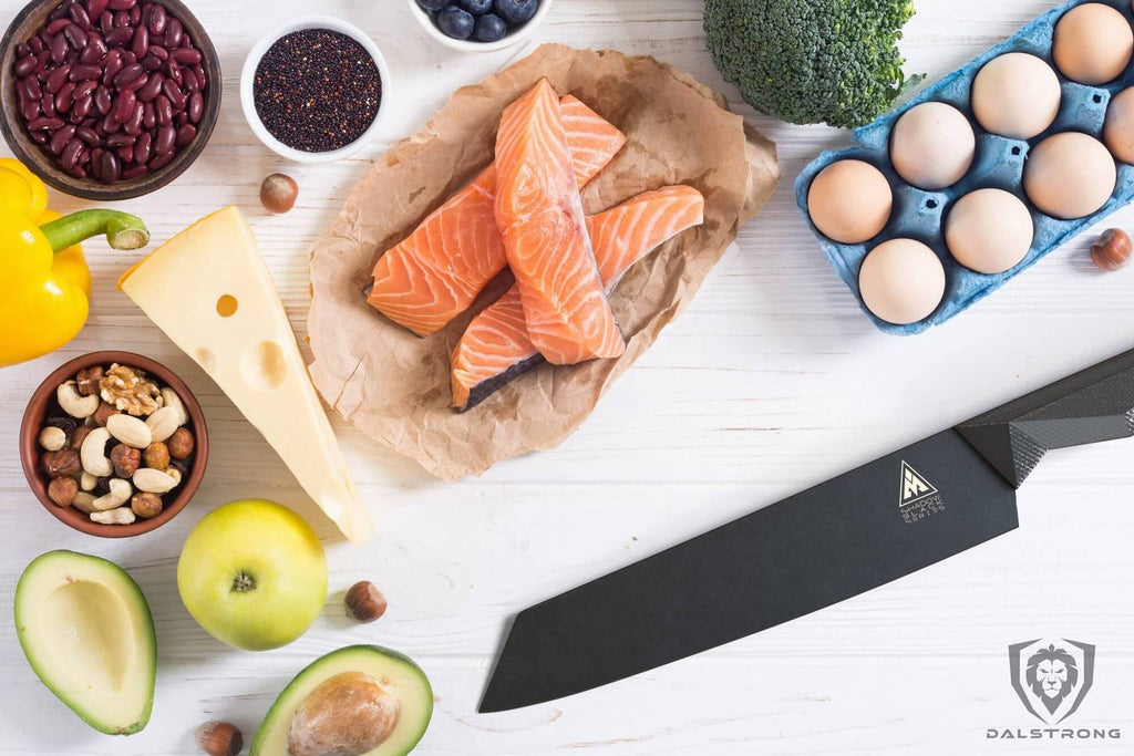 A selection of uncooked food such as salmon and eggs on a white surface next to a black chef knife