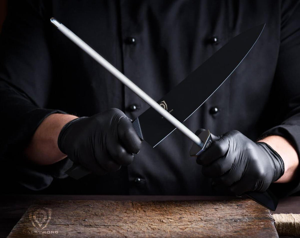 Man in black shirt and black gloves holding a chef knife in one hand a honing steel in the other