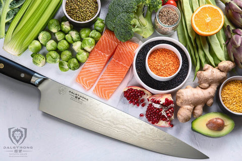 Large Kitchen knife on a white surface in front of salmon and vegetables