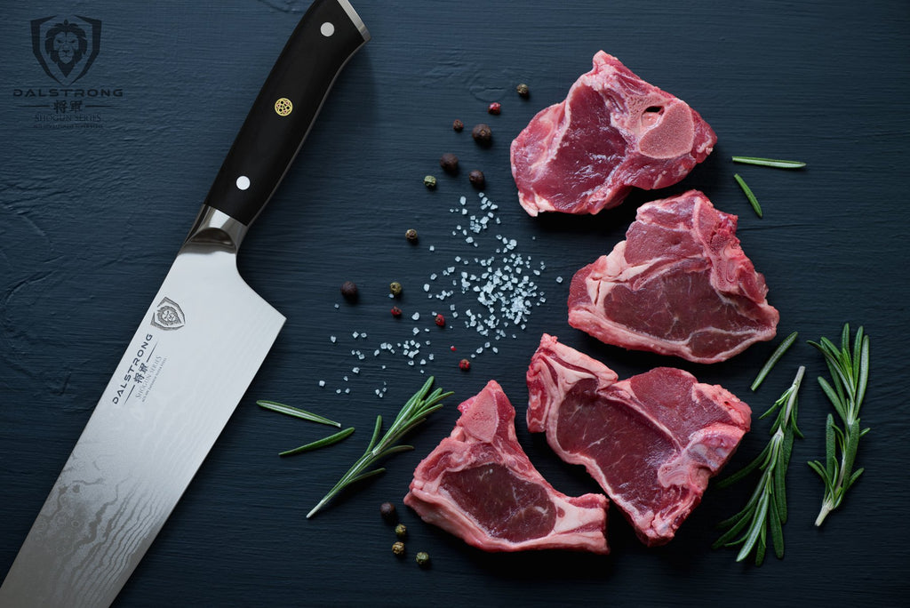 Large chef knife next to four pieces of uncooked beef