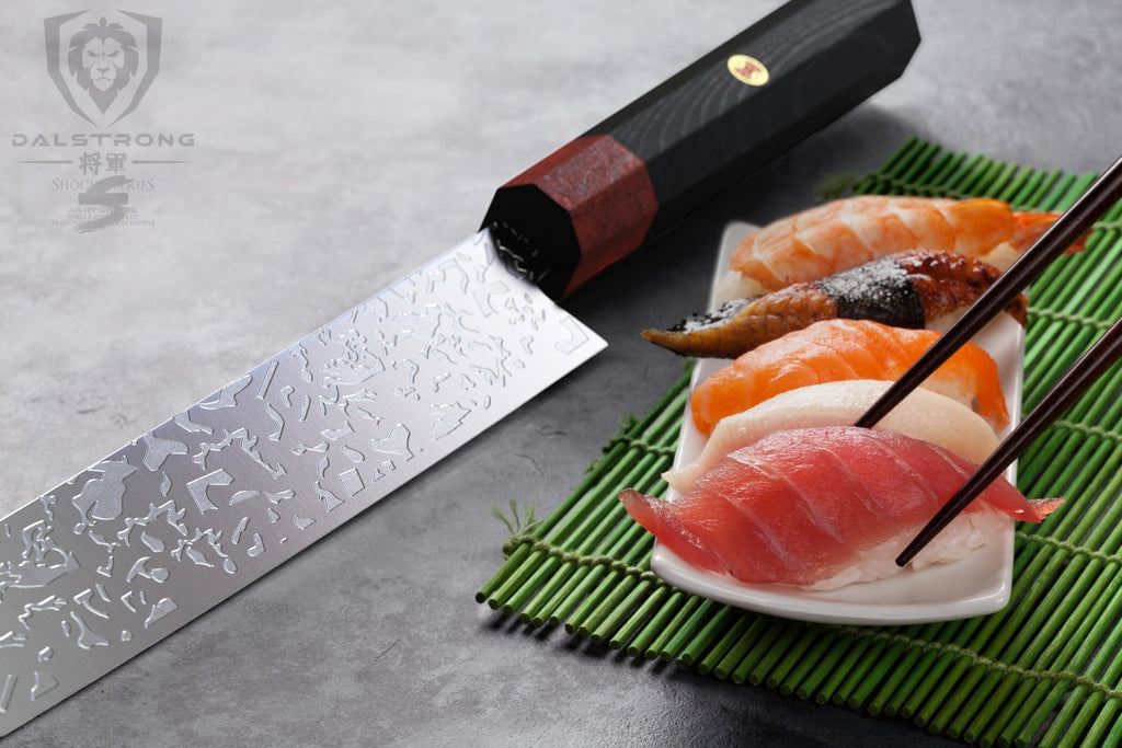Chopsticks lifting a piece of orange sushi from a plate next to a sushi knife