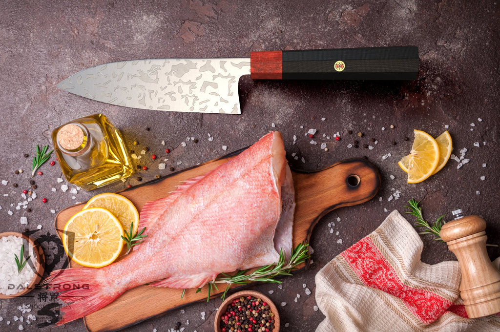 Deba knife beside a chopped raw fish on a cutting board surrounded by cooking ingredients such as salt and lemon