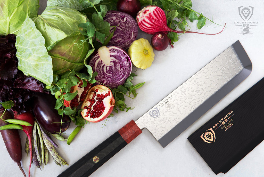 Dalstron Usuba knife on a white surface in front of a pile of vegetables including cabbage and onions