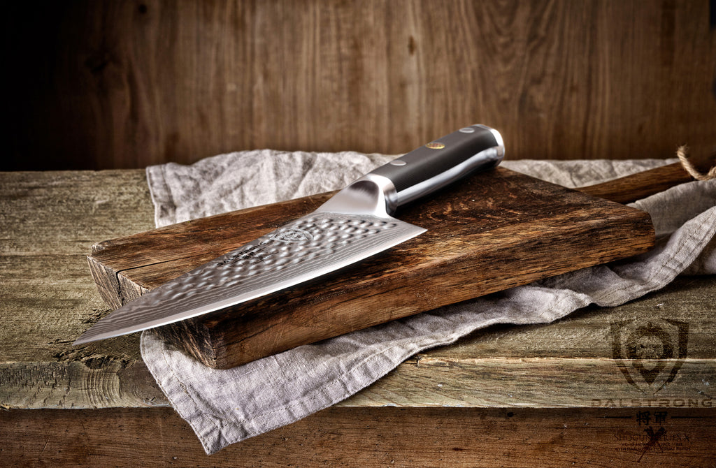 A sharp gyuto knife with damascus steel on a wooden cutting board