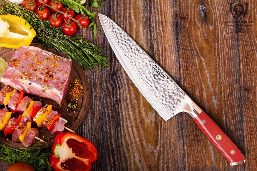 Sharp kitchen knife with red handle next to an assortment of vegetables and uncooked chicken on a wooden table