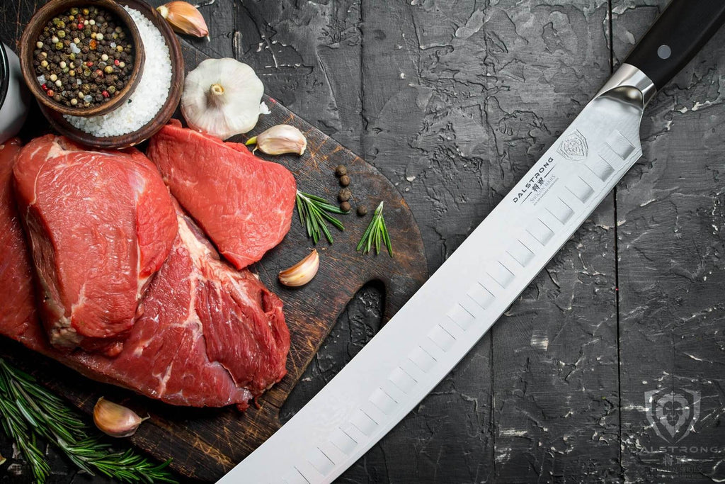 Long silver butcher knife next to uncooked meats and salts