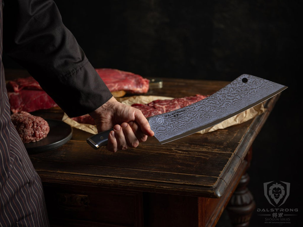 Man holds a large cleaver knife with a lot of uncooked meat on a table in the background