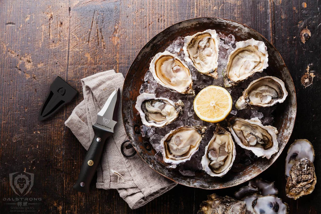 A large plate of eight oysters and garnish on a wooden counter next to an oyster knife