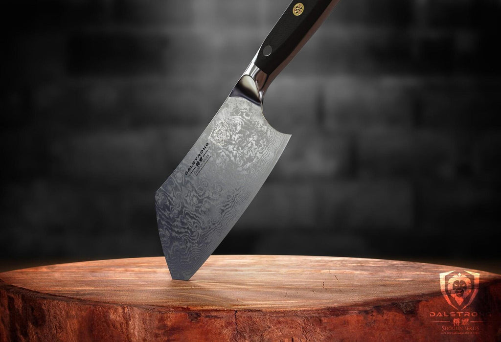 Mini cleaver with damascus steel sticking into a cutting board by the tip of the blade