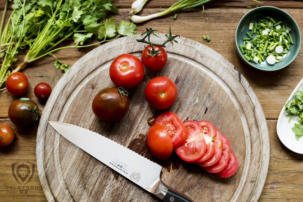 Serrated chef knife on a circular cutting board next to sliced tomatoes