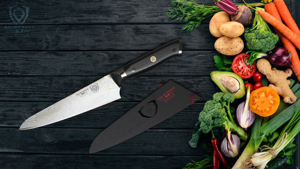 A sharp kitchen knife on a dark surface next to colorful vegetables
