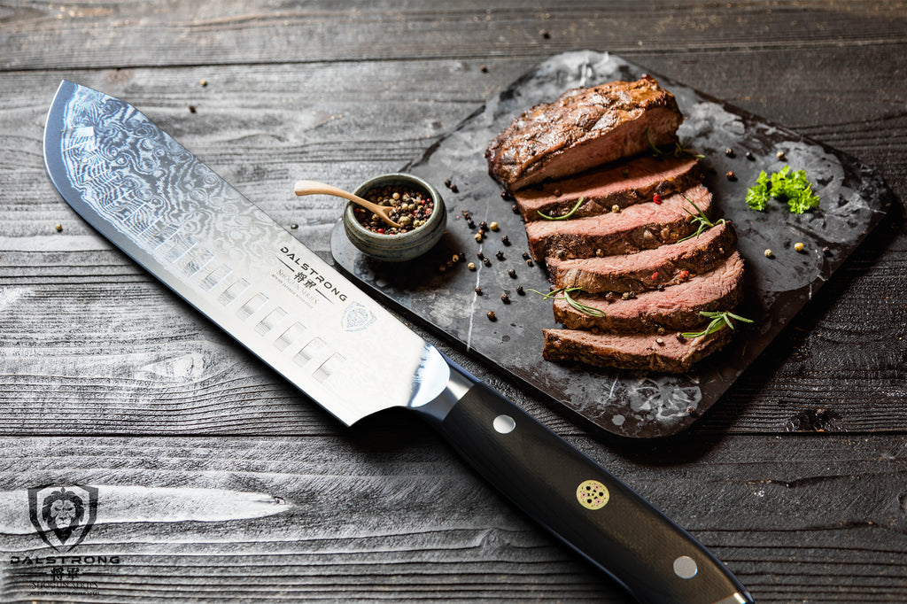 A sharp bullnose butcher knife next to sliced beef on a dark cutting board