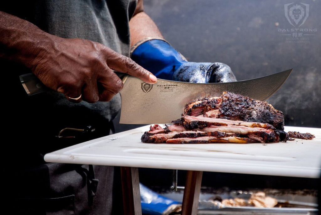 A butcher using a cleaver to slice through cooked meat on a white cutting board